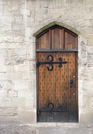 tocar la puerta: antigua puerta de madera desde la �poca medieval en la arquitectura del castillo de muro de piedra