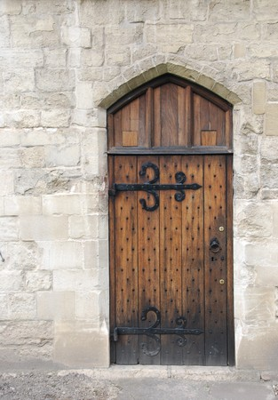 old wooden door from medieval era on stone wall castle architecture Stock Photo