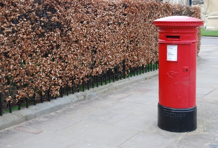 post box: red and vintage british postbox on the sidewalk Stock Photo