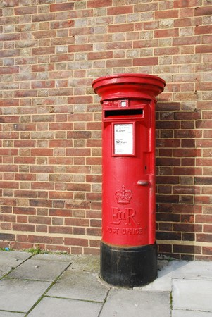 red and vintage british postbox on the sidewalk (brick building background) Stock Photo - 7185550