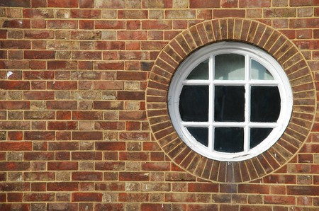 round and vintage wooden window on a brick wall building Stock Photo