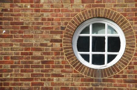 round glasses: ventana de madera redonda y vintage en un edificio de pared de ladrillo