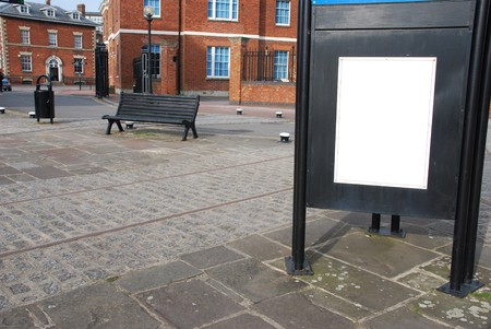 empty billboard at the sidewalk with wooden bench and typical british brick wall buildings photo