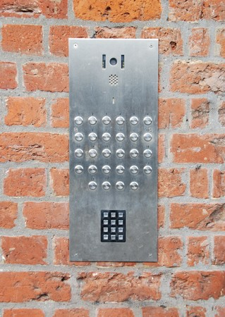 private access: close-up on a intercom doorbell and access code panel on brick wall residential building Stock Photo