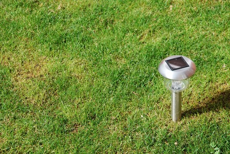 close-up of a solar garden light on green grass photo