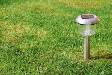 close-up of a solar garden light on green grass photo