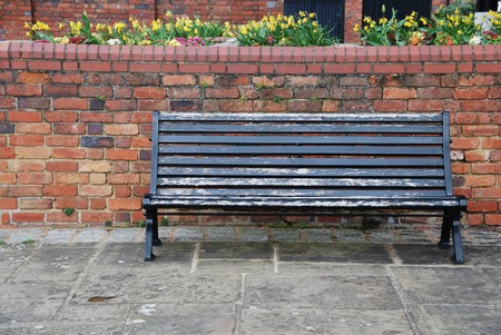 beautiful sidewalk scene with wooden bench, brick wall and flowers