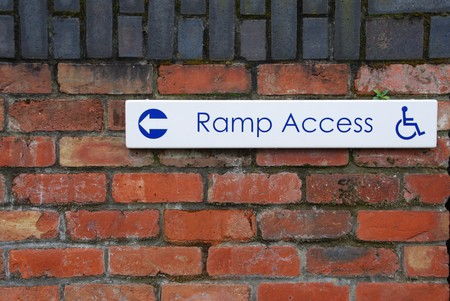 ramp access sign on a brick wall background photo