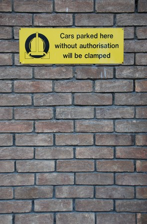 authorisation: yellow cars parked here without authorisation will be clamped sign at a grey brick wall background