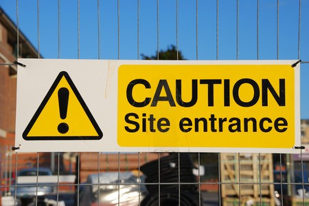 caution site entrance sign hanging on a metallic fence at a construction site photo