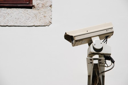 video surveillance camera on a wall (by the window)    photo