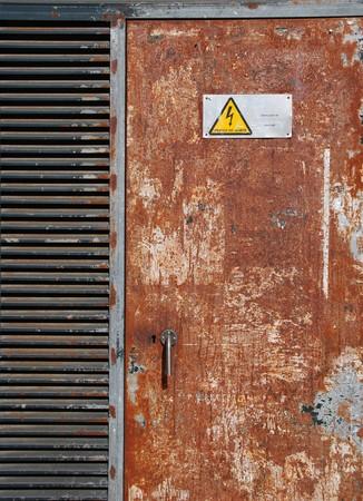 danger high voltage sign on a rusty metal door photo