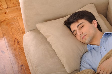 attractive young man sleeping on the couch photo