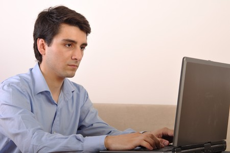 attractive young man with laptop computer sitting on the couch at home photo