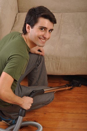 smiling young man with vacuum cleaner doing the housework Stock Photo - 7377704