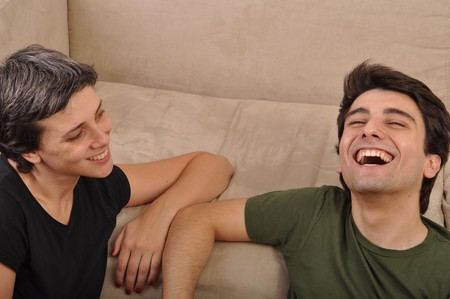 friendship between sister and brother lying and laughing on the floor next to couch photo