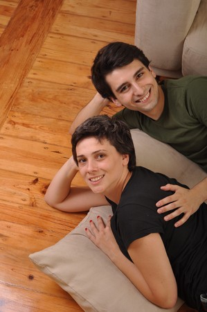 lovely friendship between sister and brother lying and relaxing on the floor next to couch photo