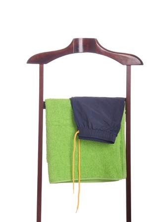 man beach clothing on a wooden hanger with green towel and blue swimsuit (isolated on white background) Stock Photo - 7508102