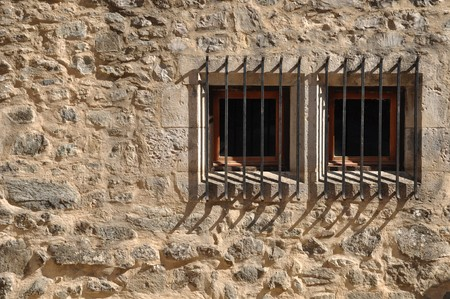 ancient windows of a medieval building with bars photo