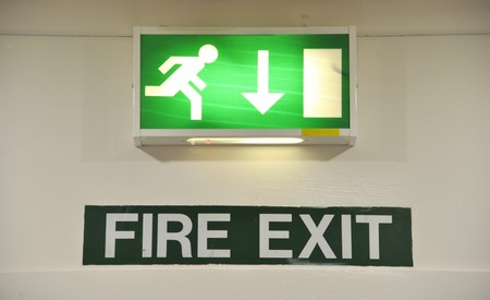 green and white warning sign glowing regarding fire exit emergency   photo