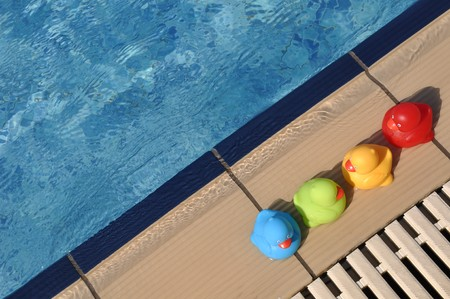 four colorful rubber ducks at the pool side (kids toy) photo