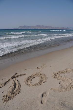 Kos written on a sandy beach in Kos, Greece (Turkey on the background) photo