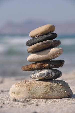 beautiful pebble stack on a sandy beach (sea on the background) photo