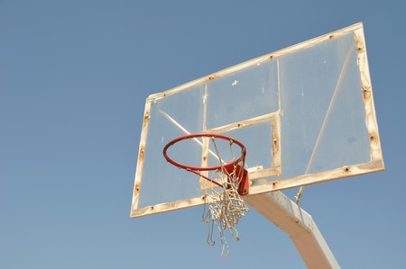old outdoor basketball hoop against blue sky background photo