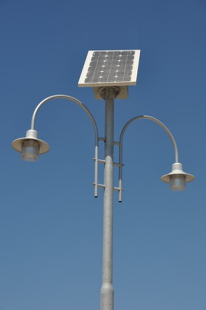 street lamp post with solar panel energy (against blue sky background) photo