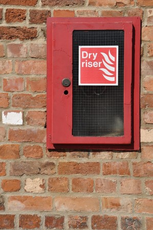 dry riser fire extinguisher inlet (brick wall background) photo