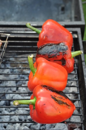 grilling red peppers on a outdoor barbecue (focus on the first) photo