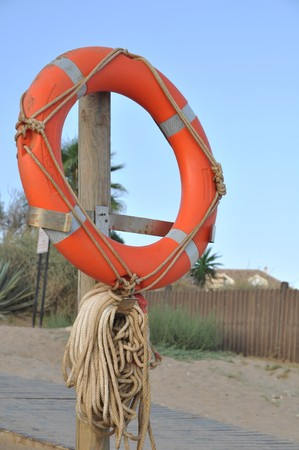 foam safe: orange buoy foam lifesaving ring at the beach (sunset picture) Stock Photo