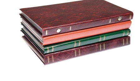 pile of antique photo albums isolated on white background photo