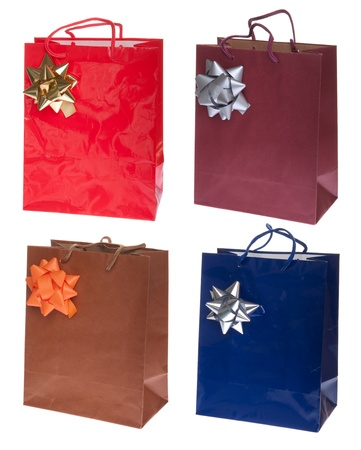 four colorful gift paper bags with bows isolated on white background photo