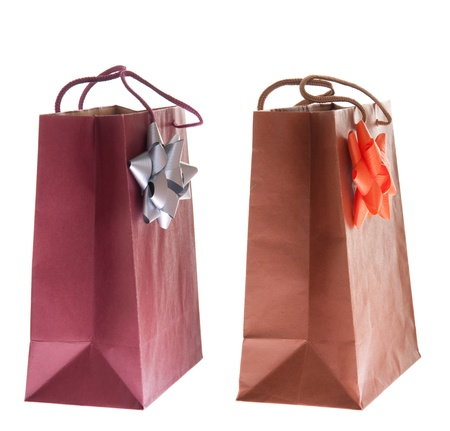 two colorful gift paper bags with bows isolated on white background photo
