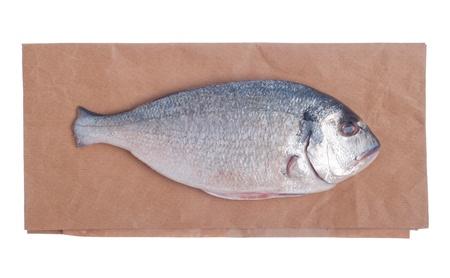raw dorado fish on market paper bag (isolated on white background) photo