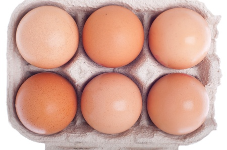 detail of six eggs in a carton box isolated on white background photo