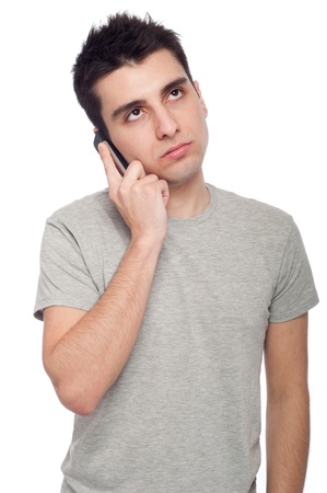 cellular telephone: worried young casual man talking on the phone (isolated on white background)