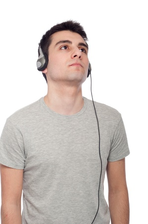 quiet casual young man listening music on headphones (isolated on white background) photo
