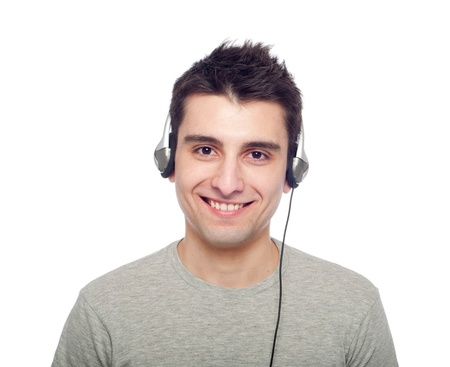 smiling young man listening music on headphones (isolated on white background) photo