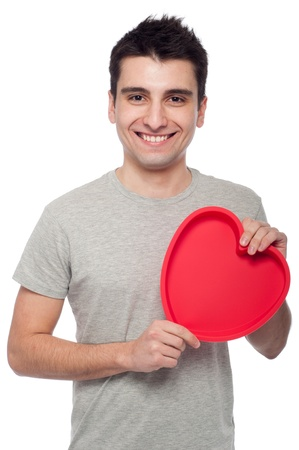 lovely portrait of a young man holding a red heart (isolated on white background) photo