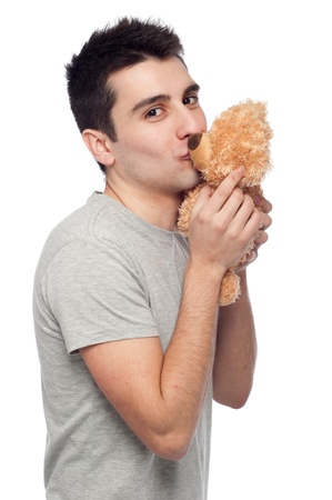 lovely portrait of a young man kissing a teddy bear (isolated on white background) photo
