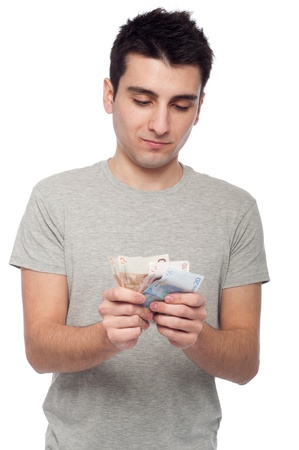 quiet young man looking at his money, euro bills (isolated on white background) Stock Photo - 8818379