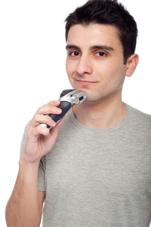handsome young man shaving with electric shaver (isolated on white background) photo