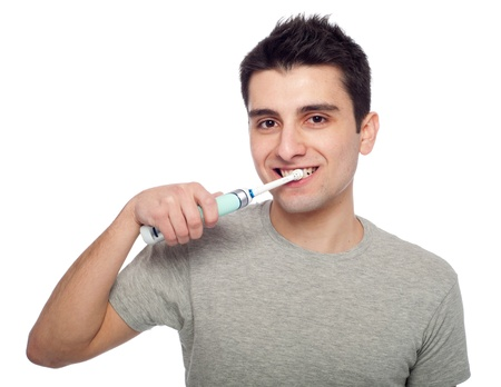 dentalcare: handsome young man brushing his teeth with electric toothbrush (isolated on white background)