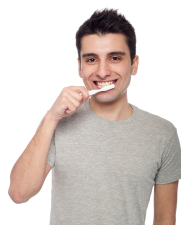 handsome young man brushing his teeth with toothbrush (isolated on white background) photo