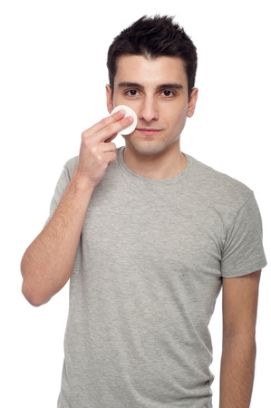 handsome young man cleaning face with cotton swab (isolated on white background) Stock Photo - 8832484