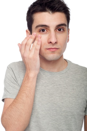 rejuvenate: handsome young man applying eye cream for dark circles (isolated on white background) Stock Photo