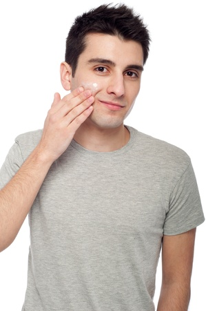 handsome young man applying cream lotion on face (isolated on white background)