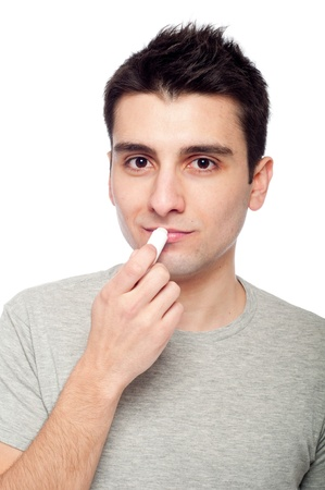 handsome young man applying lip balm (isolated on white background) photo